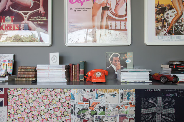 Grey walls form a lovely backdrop for colorful books and knick-knacks
